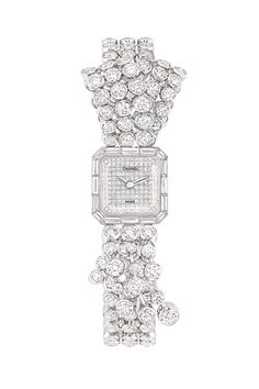 The Ruban Mademoiselle watch in 18K white gold set with 336 round-cut diamonds, and 16 baguette-cut diamonds.    - ELLE.com