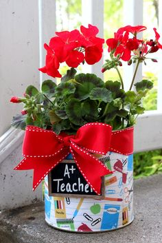 Super easy project. Put scrapbooking paper around a coffee tin and tie a ribbon around the top to make an adorable flower pot!