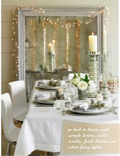 white and silver holiday table setting and large mirror with twinkle lights