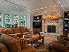 A plush sectional sofa and two brown leather armchairs provide comfortable seating in the basement. Built-in bookshelves flank the stone fireplace, which features a fish on the mantel, a nod to the lake setting. Basement Family Rooms, Game Room Basement, Modern Basement, Basement Ideas, Basement Layout, Basement Inspiration, Basement Remodeling, Remodeling Ideas, Other Rooms