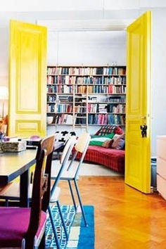 The Look: A sunshine-y shade is the perfect entrance to a casual living room/library. Because yellow coordinates well with many different colors, this hue is a lovely choice that incorporates both the colorful bookshelves from the living room and the dining room furnishings from the kitchen area.    The Color: Try Benjamin Moore Bright Yellow 2022-30.