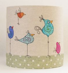 A quirky handmade drum lampshade, created with high quality linen and cotton fabrics, featuring a row of colourful cartoon birds marching around the base.  I create each using high quality linen and cotton fabrics, embellished with applique and free-machine embroidery and signed with my machine embroidered signature.  As each piece is individually made to order, no two will ever be the same. The lampshade is available in two sizes:  20cm diameter x 20cm h 30cm diameter x 20cm h  If you…