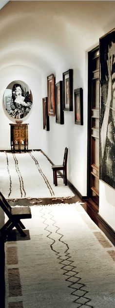 white and wood + moroccan rugs + hallway art display