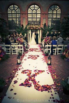 A gorgeously romantic wedding ceremony at Biltmore Estate (Conservatory venue). Flowers by Flower Gallery of Asheville.
