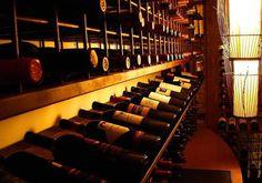 """Dica: Garrafa de vinho deve ser guardada na horizontal  Isso se explica pelo fato de que, se mantida na vertical, o vinho não entrará em contato com a rolha, geralmente feita de cortiça, uma fibra vegetal. O contato da rolha com o vinho potencializa o processo de vedação, impedindo assim a entrada de ar na garrafa e, por consequência, sua acidificação ou """"avinagramento""""."""