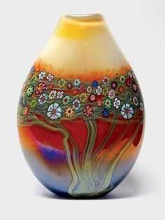 """""""Mango Vines Pouch""""  by Ingrid and Ken Hanson - the rainbow-colored bouquet of handmade murrini flowers and the flowing branch motif is spectacular.  The iridescent surface gives a subtle sheen to this dazzling hand blown glass vase..."""
