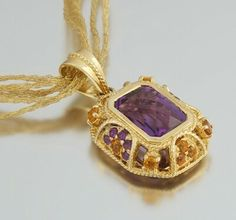 """14k yellow Gold pendant set in the center with a checkered-cut Amethyst, .14 x 10 mm, and further enhanced with smaller Amethysts and Citrine, measures . 1""""L x¾""""W; suspended from a six-strand mesh Gold necklace, . 17"""" long. Overall weight . 16.8 gm."""