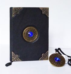 genuine leather writing and pendant, of two. The journal is decorated with a bronze plated blue glass pendant beautiful antiqued, and filigree ornaments in corners. The same amazing on a long leather strap is the part of the set. Leather Notebook, Leather Journal, Leather Gifts, Leather Jewelry, Leather Photo Albums, Handmade Notebook, The Secret Book, Notebook Ideas, Small Shops