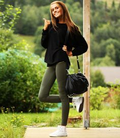 olive green skinny jeans, oversized black sweater, and all-stars