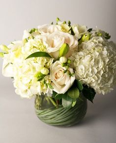 Stunning all-white premium flowers such as hydrangea, roses and lilies with green berry accents.