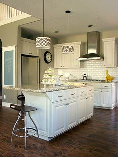 My new kitchen will look a lot like this.  Distressed floors, white cabinets, light beige walls, subway tile, stainless hood over gas stove, granite countertops.  My island will be a bit bigger and will have three stainless adjustable lights above it. Should be finished (mostly) in just a few weeks. ~ Susan