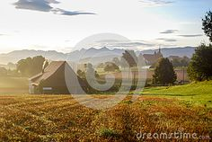 The sun is rising over a village in the Swiss Alps. Agricultural landscape with a field in the foreground, houses and a church in the back and mountains in the background. Swiss Alps, Travel Destinations, Tourism, Sunrise, Hiking, Europe, Houses, Stock Photos, Mountains