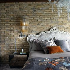 French style bed in front of exposed brick wall