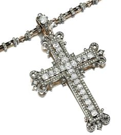DIAMOND CROSS PENDENT NECKLACE,  1880S.  The Latin cross embellished with scroll and stylised fleur de lys motifs, set with cushion-shaped, sinle- and rose-cut diamonds, to a chain designed as a series of rectangular links accented with diamond set trefoil elements, length approximately 470mm.