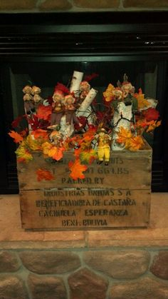 Birch logs in an old wooden box decorated with leaves & little pumkin people