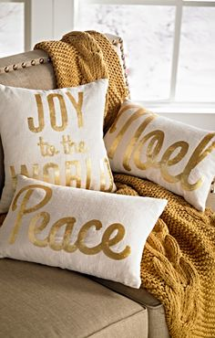 Words of glad tidings are formed by shiny gold sequins, and the flourishes of a script typeface enhance the elegance of these holiday pillows.