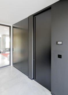 zwarte binnendeur zonder kozijn en een ingebouwde handgreep