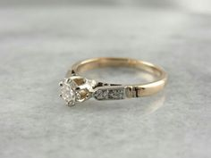 """This sweet vintage ring is from the '40's, and is a wonderful combination of yellow gold and platinum, polished shine and interesting lines. The center stone is just under a quarter carat, a bright gem with plenty of glitter and flash!  Metal: 14K Yellow Gold, Platinum Gem: Diamond .23 Carat, J in Color, SI in Clarity Gem Measurements: 3.9 mm, Round Accents: 4 Diamonds totaling .06 Carat Ring Size: 3.50 Marks: """"14K JI AT"""" Stamped on the inside band"""