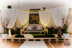 Rustic garden wedding dais or pelamin with fresh flower (phalaenopsis orchids, hydrangeas, roses) wall and cherry blossom trees.