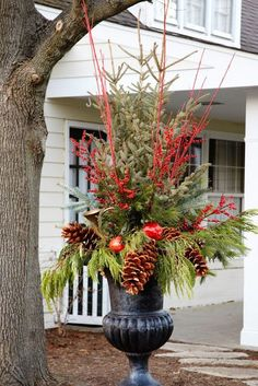 Tall, Stunning Winter Urn featuring large Pine cones, Red Dogwood, and All-Weather Berries.
