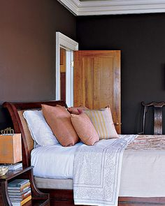 "Charleston, South Carolina, homeowner Clare Pernice's affection for the way paint ""gets really absorbed into the walls of old places"" prompted her to treat the guest room with a deep, matte chocolate. ""I wanted it to feel velvety and intimate,"" she says. Accent colors like the pale greens and oranges of the antique crewelwork bedspread keep the darkness from becoming overwhelming. The overall effect makes it a very restful spot."