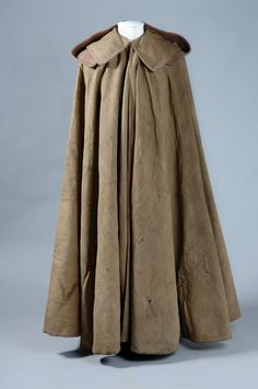 Dark green full length cloak of green serge lined with red serge, with wide collar and detachable hood.Major James P. Wolfe was a British Army Officer who achieved posthumous fame after defeating French forces on the Plains of Abraham in 1759, allowing the British to take Quebec, which led in turn to the capture of Montreal and the end of French control of Canada. He was killed on the Plains of Abraham and was reputedly lain on this cloak in his final moments. He is immortalised in the…