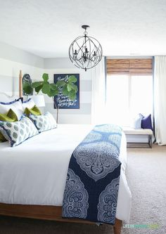 Guest bedroom with woven shades, ribbon trimmed drapes, white bedding, navy blue paisley throw, Doxology canvas, fiddle leaf fig tree, chartreuse velvet pillows and hickory wood bed via Decked and Styled Spring Home Tour - Life On Virginia Street