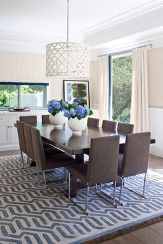 Gorgeous dining room with ivory and blue geometric rug over hardwood floors. Incredible white quatrefoil pendant over modern dark wood trestle dining table and taupe dining chairs with chrome legs. dining room with tan paint color on top half of walls and white wood panels on bottom half of walls. Floor to ceiling ivory drapes with blue ribbon trim covering dining room windows.