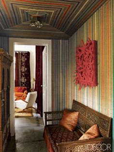 <p>Artist Nabil Nahas upholstered the walls and ceiling of the hallway in his Beirut apartment in a striped fabric found in a Damascus souk.</p>