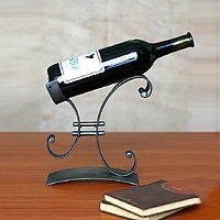 NOVICA Iron wine bottle holder, 'Close to You' by NOVICA. $57.95. Lyrical and lovely this handcrafted sculpture holds a wine bottle. Marco Florindez shapes steel arcs that move close together then outward again. This was designed with couples in mind he says. The human being is complex but when all is said and done we are our partner's complement. One can't live without the other. Wine not included.