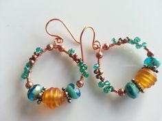 """Golden lampwork bead, star shaped spacers of brushed sterling silver, blue-green Picasso Czech fire-polished rondelles, teal colored wired-wrapped Czech glass, copper plated beads , and metallic gold iris colored Czech fire-polished beads.     Finished size: 1 1/2"""" long x 1 3/8"""" wide in diameter    Features  • Ear wire stoppers recommended & included  • Gift box of colorful turquoise included with instructions for maintaining copper jewelry naturally  • Unique, high quality craftsmanship…"""
