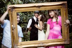 Bride kissing the groom after wedding posed with antique frame in the foreground held up by flower girl and ring barrier.