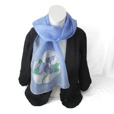 In a soft violet-blue shade with white and green floral design, it makes a perfect gift. The light natural fabric keeps you warm in winter and cool in summer meaning it is an ideal gift for any loved one.  This unique artwork has been hand painted on a 100% silk scarf which is sumptuously soft and light to wear. It makes a stunning gift or a perfect treat for yourself. Purple Scarves, Silk Scarves, Cotton Shopping Bags, Silk Painting, Fast Fashion, Wearable Art, Floral Design, Feminine, Hand Painted