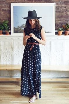 Black hat, printed black dress,  brown belt