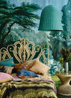 Bohemian Bedroom done up just right in peacock blue, moss green, and violet; backed by dramatic wall mural and iconic white wicker headboard. Dramatic wicker lamp highlights the overall decor.