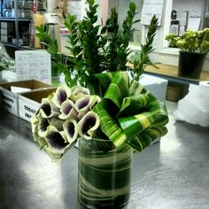 A cluster of picasso callas and aspidistra variegated leaves that folds into a ribbon.
