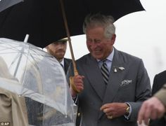 Prince Charles speaks with Lieutenant Governor of Manitoba Philip S. Lee, right, as Camilla, the Duchess of Cornwall struggles with her umbrella 20 May 2014