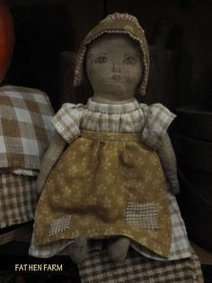 "Fat Hen Farm - Primitive Rag Doll - Early Brown Homespun & Calico... She is wearing lovely homespun and calico. The color is a soft mustardy brown. Her face is lightly inked and I've stuffed her with cloth giving her a nice weight. She is stitched completely by hand, signed and dated. Approx.. 10 1/2"" tall. A signed and dated Fat Hen Farm original."