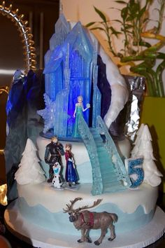 """- Disney """"Frozen"""" themed birthday cake. Castle and stares made from Isomalt, trees made from fondant. Mountain rice crispy covered with fondant and airbrushed."""
