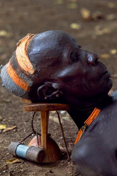 An elder of the Karo tribe rests with his head on his wooden head-rest which protects his elaborate clay hairdo. Every man carries a headrest which often doubles as a stool. This man has attached his snuff box to it. Duss, Omo Valley, Ethiopia | ©John Warburton-Lee