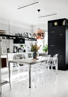 Great black and white kitchen, with great elements like the tile, ghost chairs and that copper light fixture