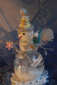 This delightful snowman is just full of tinsel and cheer. The head is made of styrofoam with a splash of glitter. His hat is made out of a piece of vintage sheet music , tiinsel and a pom-pom.Tinsel chenelle stems make up the arms. She carries a mini Christma tree and snowflake. Around her neck are various holdiday trims and ribbons. Inside the bottle is glittler, pearls and fake snow. She sits upon a felt snowflake.  Height: 7 1/4   Width: 4