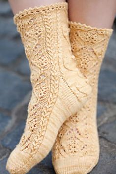 Knit from the top-down, this sock begins with a picot edging and moves into a complex, feminine cable-and-lace design down the front of the sock and a floral vine motif down the back of the leg and the heel flap.