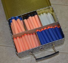 Nerf Ammo Box. This is a standard tin lunch box with dividers hot-glued in place. Fits Nerf darts to protect them from being dented by being stored loose with the Nerf guns.
