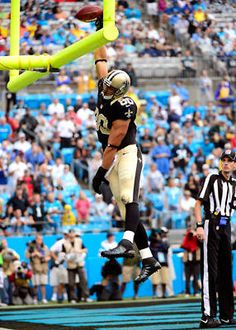 Saints tight end Jimmy Graham dunks the ball home after catching a first-half touchdown pass.