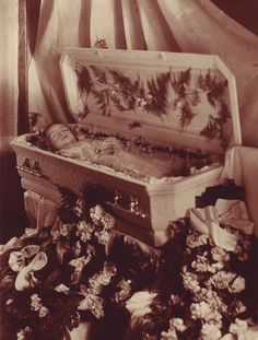 A matte silver print showing a baby in a white coffin. The photographer is Lubowicz of Colby, Wisconsin, if the matt in which it is housed is the one with which it was originally paired.