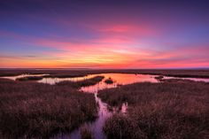 Landscape HDR photograph of pastel color cirrus clouds over the salt marsh at sunset