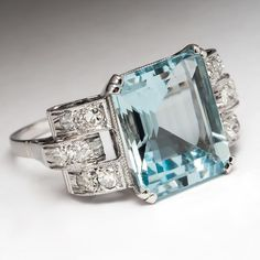 Retro Aquamarine Cocktail Ring. This gorgeous retro vintage cocktail ring features a centered emerald cut 6.65 carat natural aquamarine. The stone is set in a gorgeous scrolling solid 18k white gold mounting with sparkling accent diamonds. This ring is previously owned and in good condition.