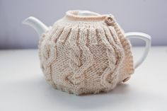 Cream hand knitted tea cosy with cable pattern and wooden button detail.. £16.00, via Etsy.