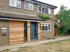 Using cedar wood, contemporary hardware and lighting this front of house is now warm and welcoming Porch Doors Uk, Porch Oak, Porch Timber, Brick Porch, House Front Porch, Front Porch Design, 1930s House Exterior, Bungalow Exterior, House Paint Exterior